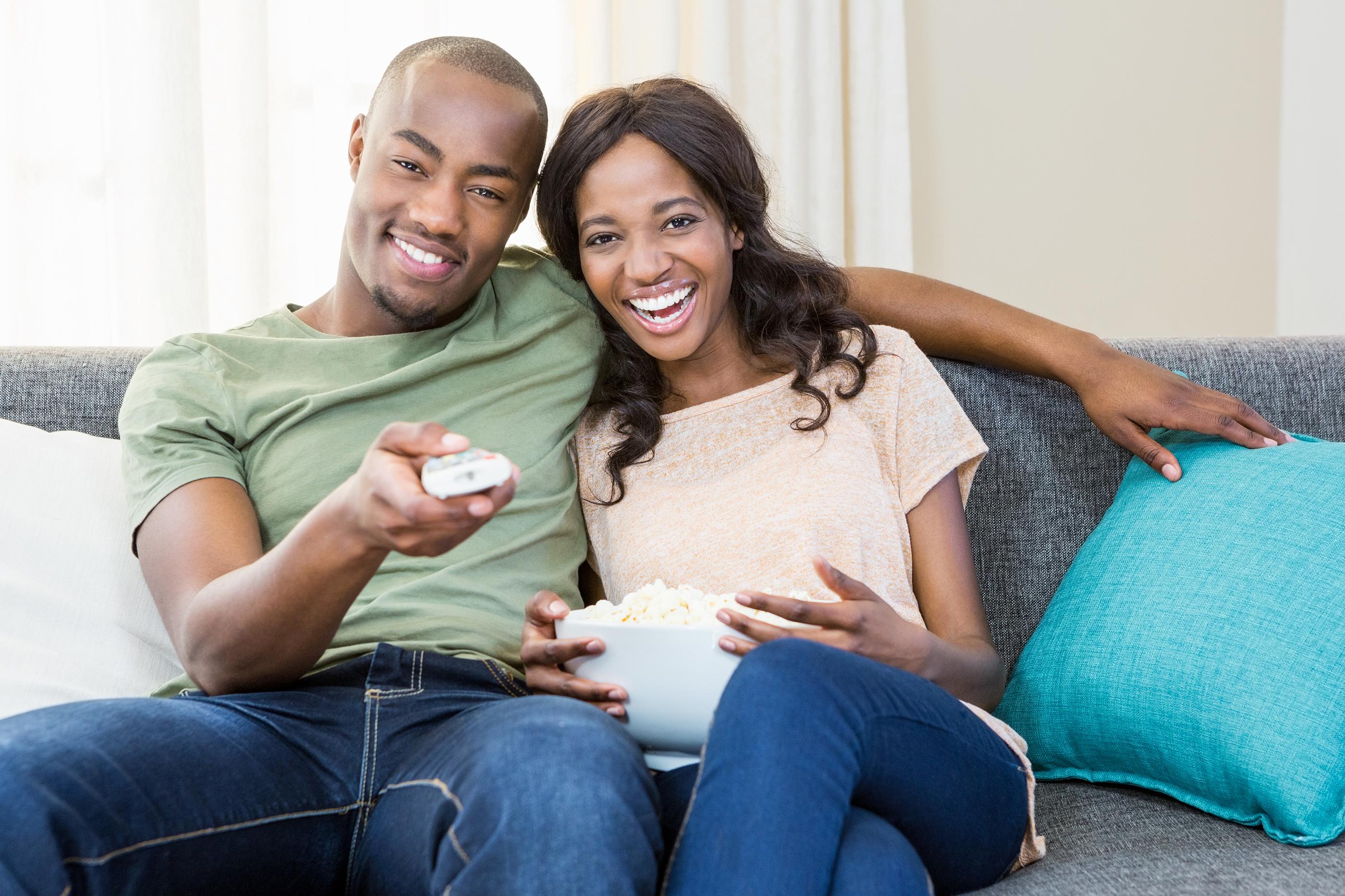 couple watching tv eating popcorn