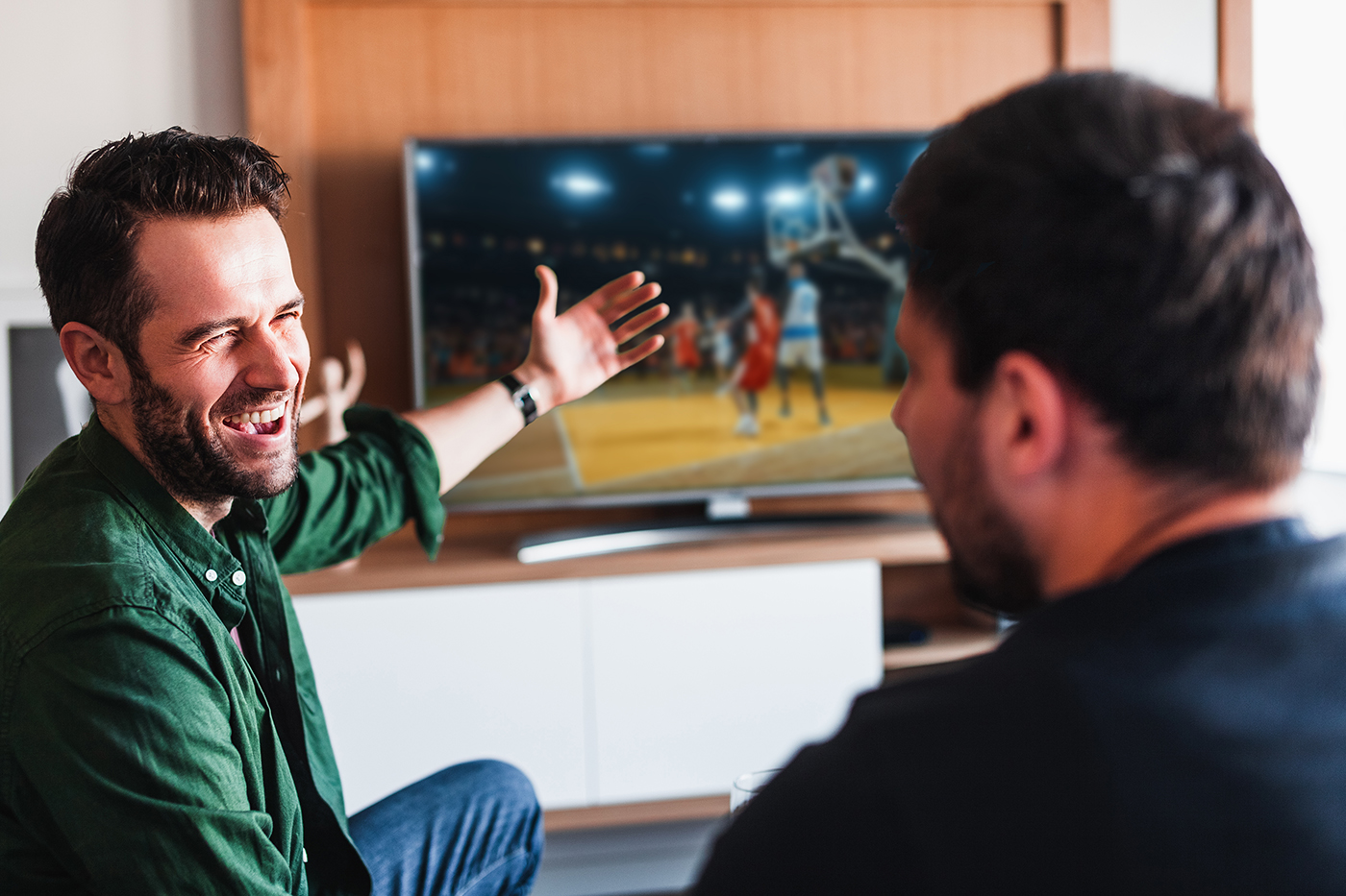Two friends watching basketball on the tv
