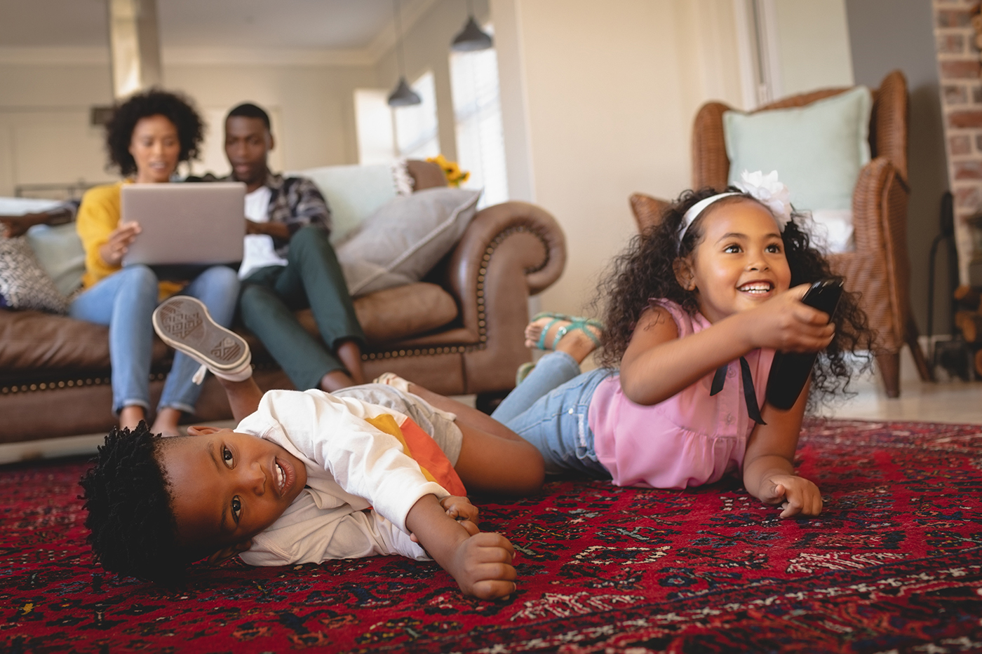 kids watching tv with parents in background
