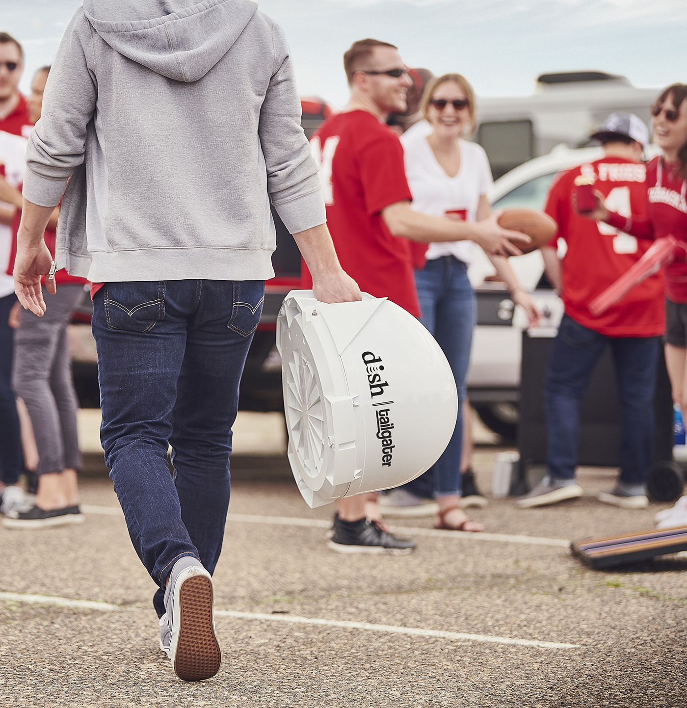 man carrying the DISH tailgater to tailgate party