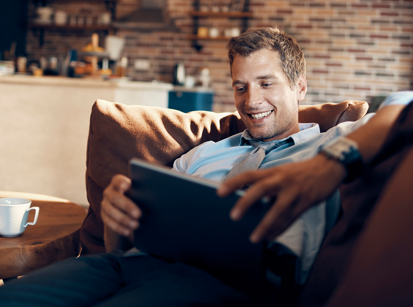 man on couch watching tablet