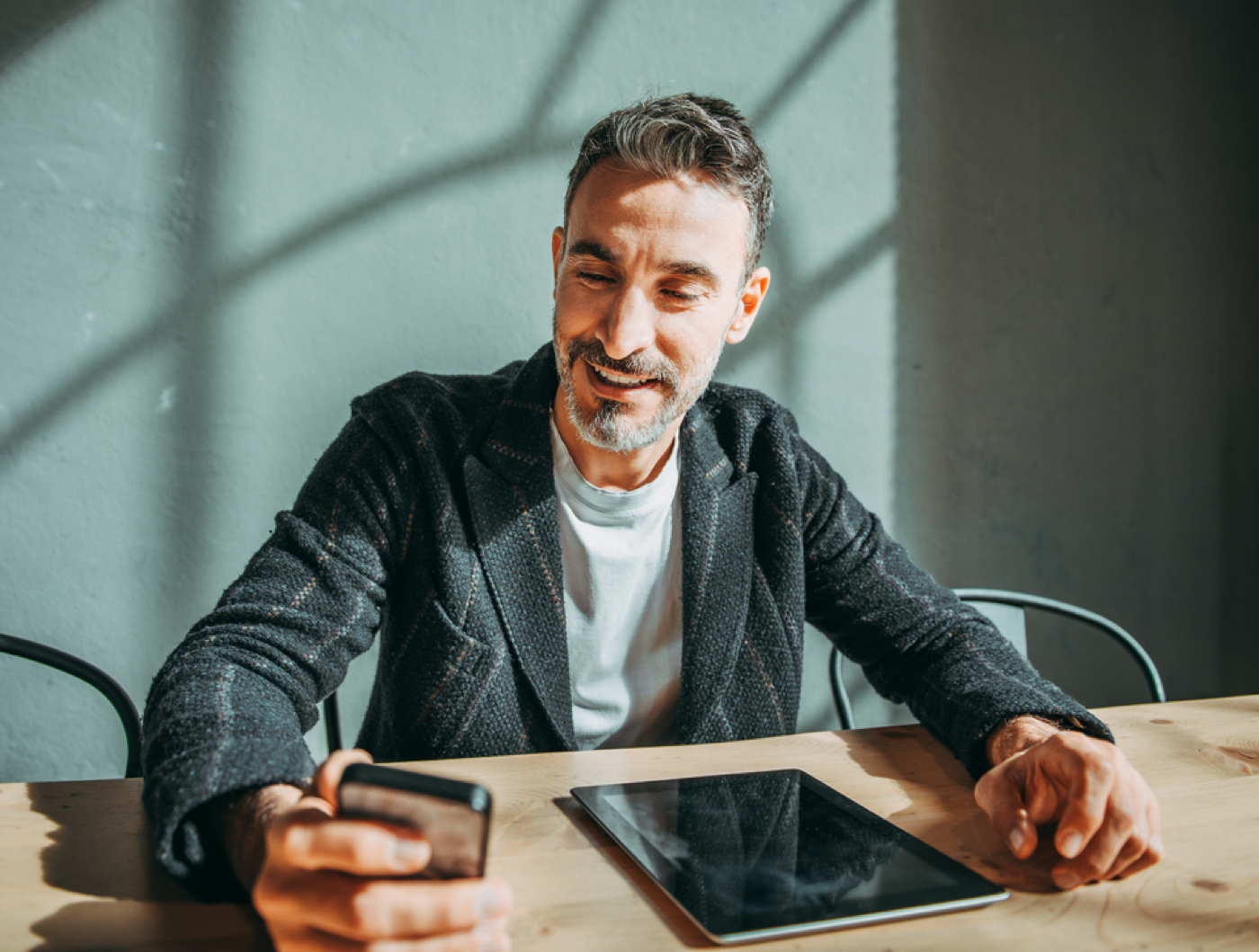 business man sitting at desk looking at his cell phone and tablet