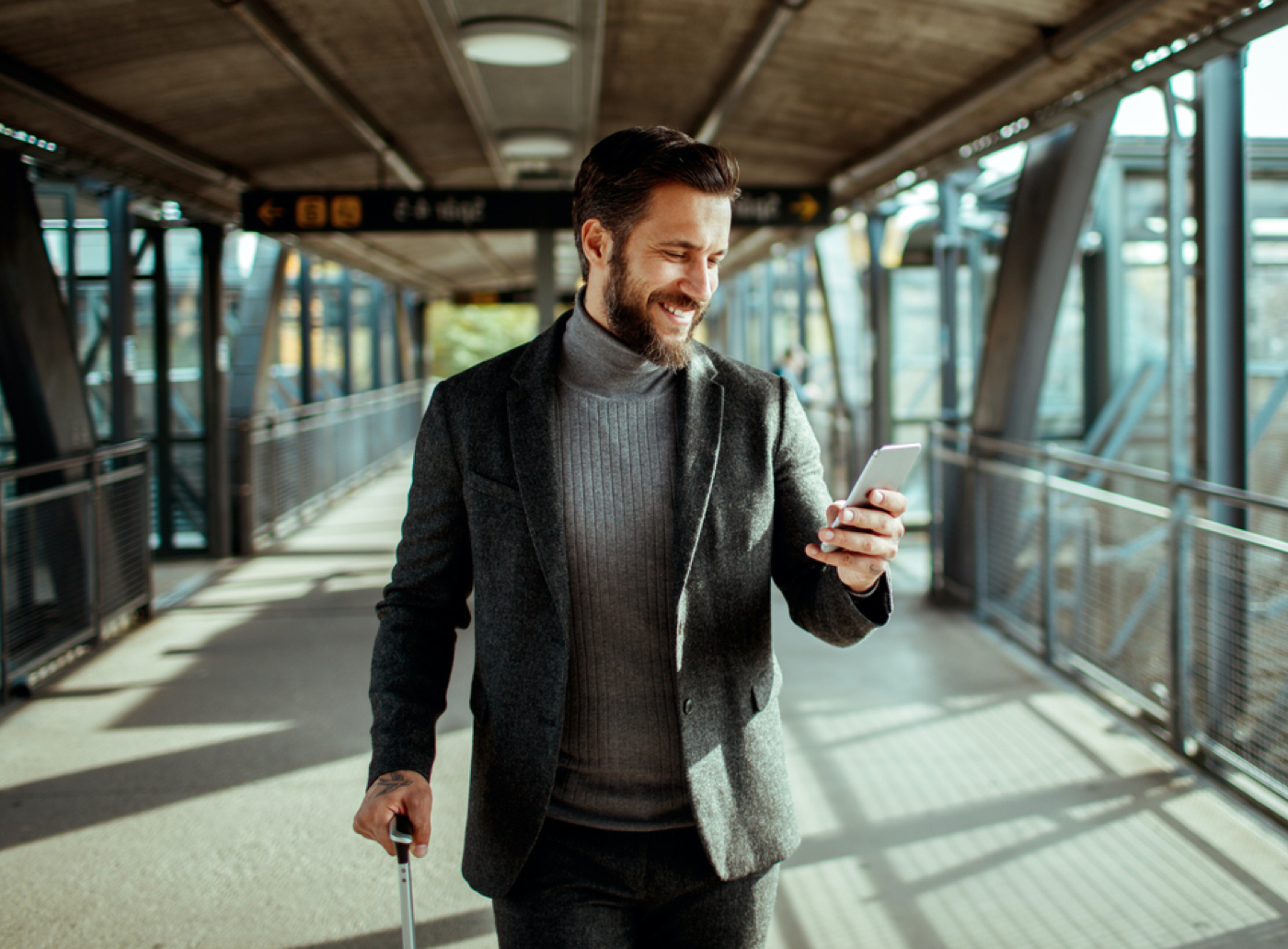 smiling man walking with luggage checking his cell phone