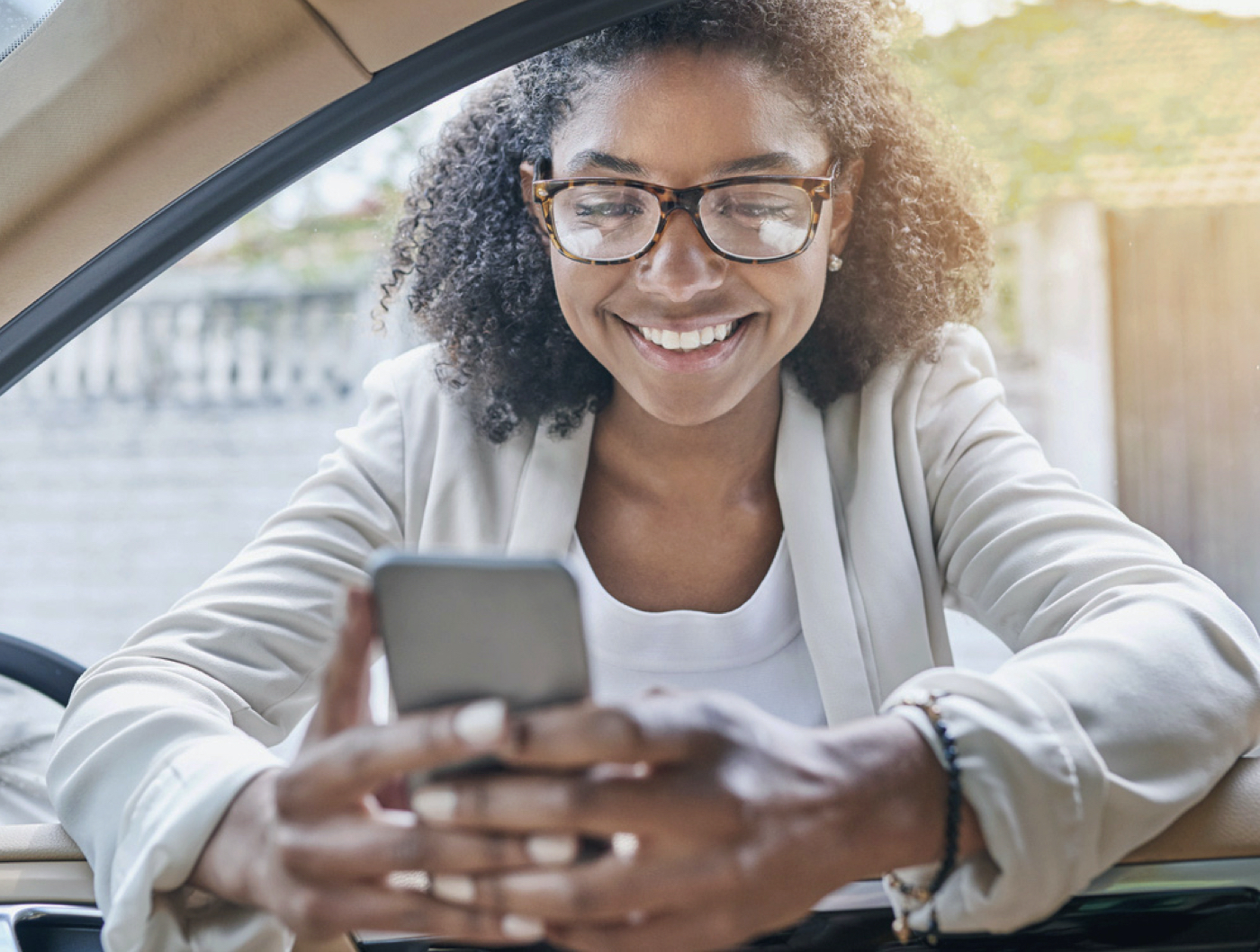 young woman leaning on car while looking at her cell phone