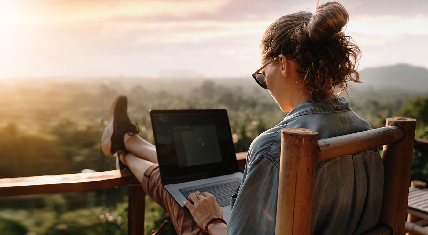woman using laptop overlooking scenic valley