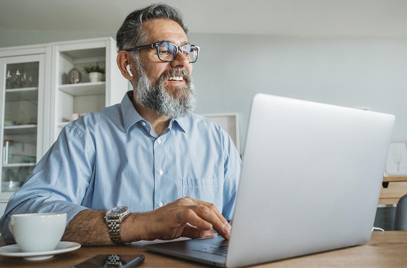 Man sitting at kitchen table looking at laptop