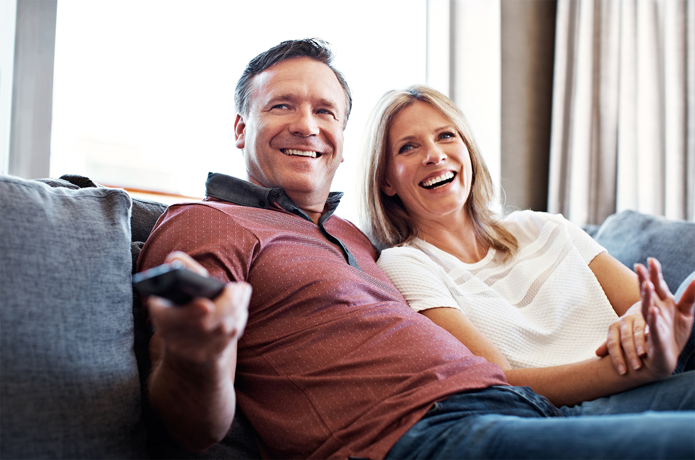 couple on couch using tv remote control