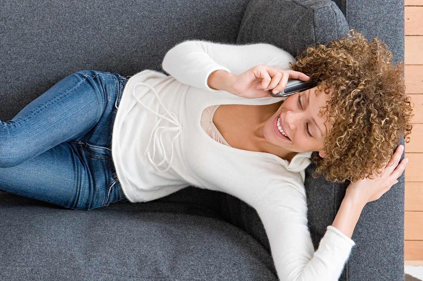 Woman lying on couch while talking on phone