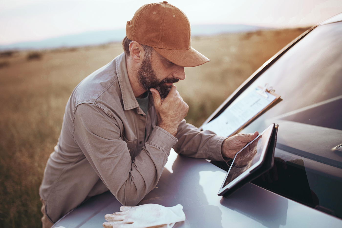 man using tablet next to truck