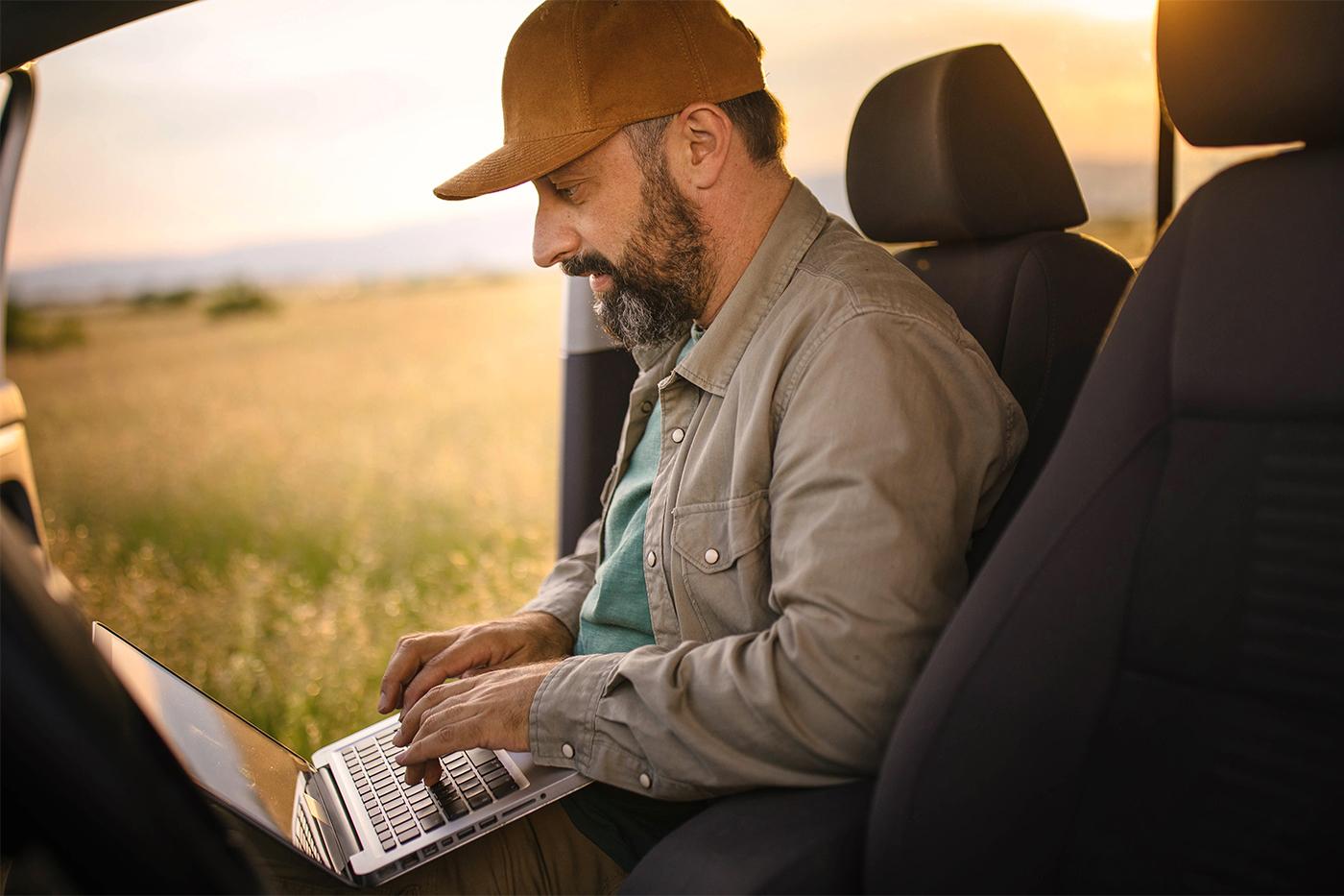 man working on laptop inside of truck