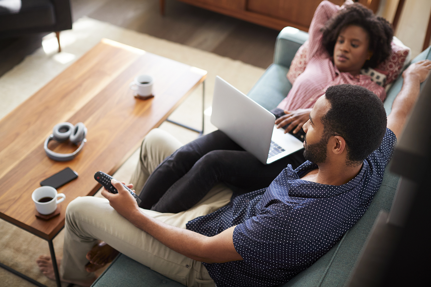 couple sitting on couch while using laptop and watching tv