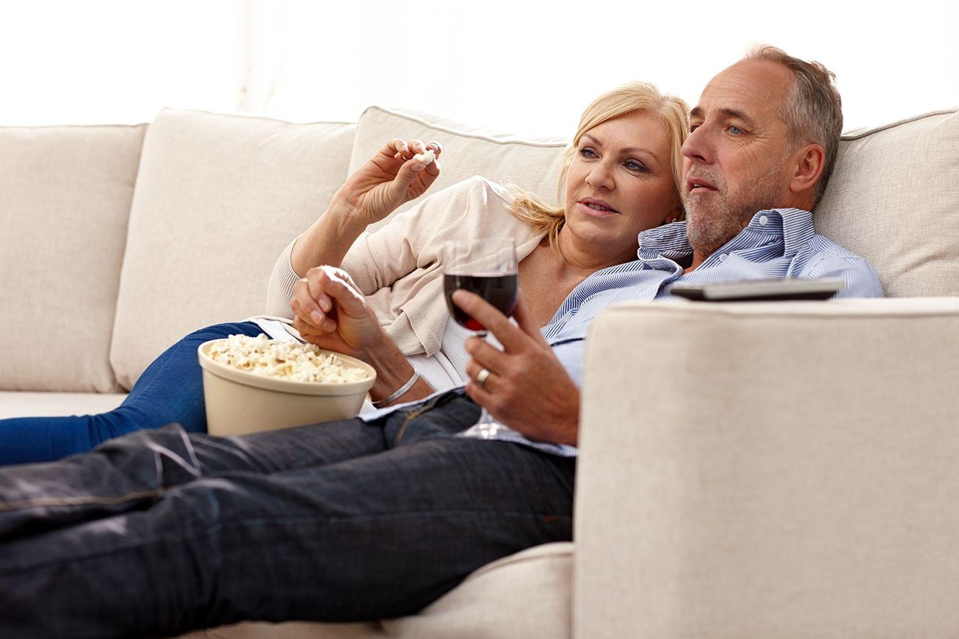 couple watching movie while enjoying popcorn and wine