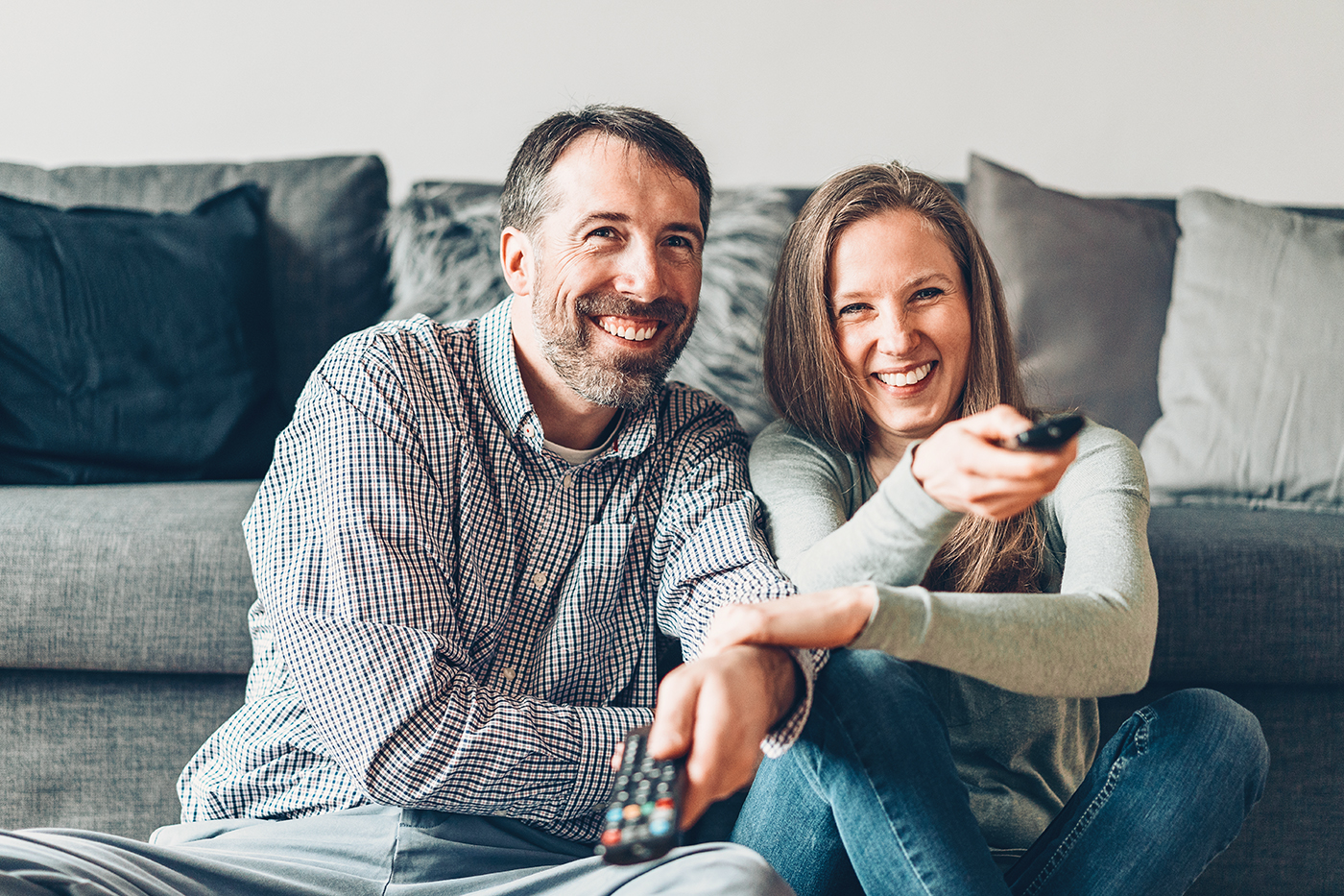 couple on couch fighting over tv channel
