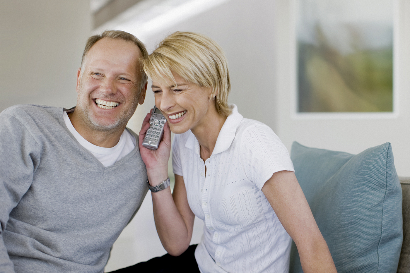 couple on couch talking on phone