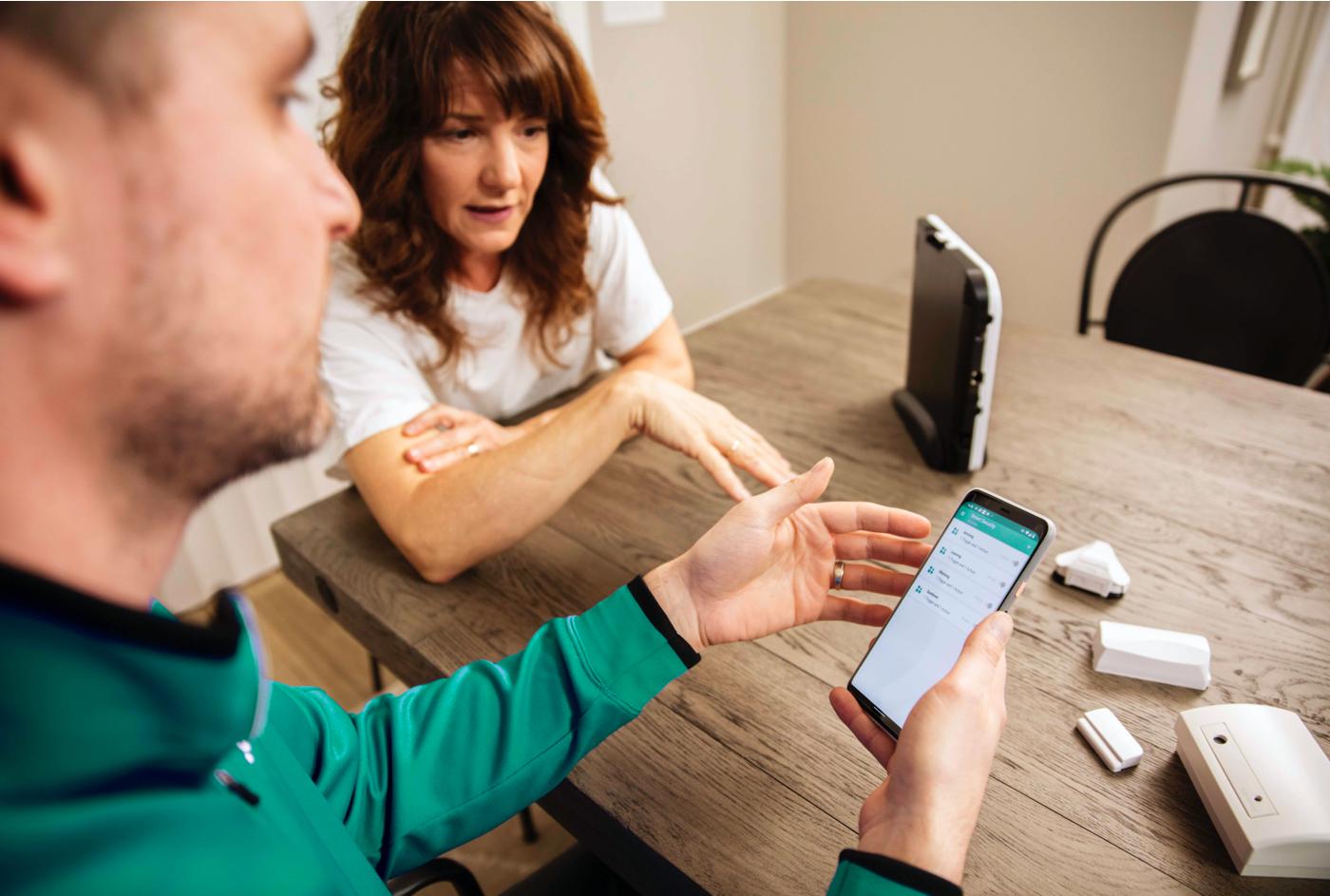 An installer helps a customer understand app and equipment