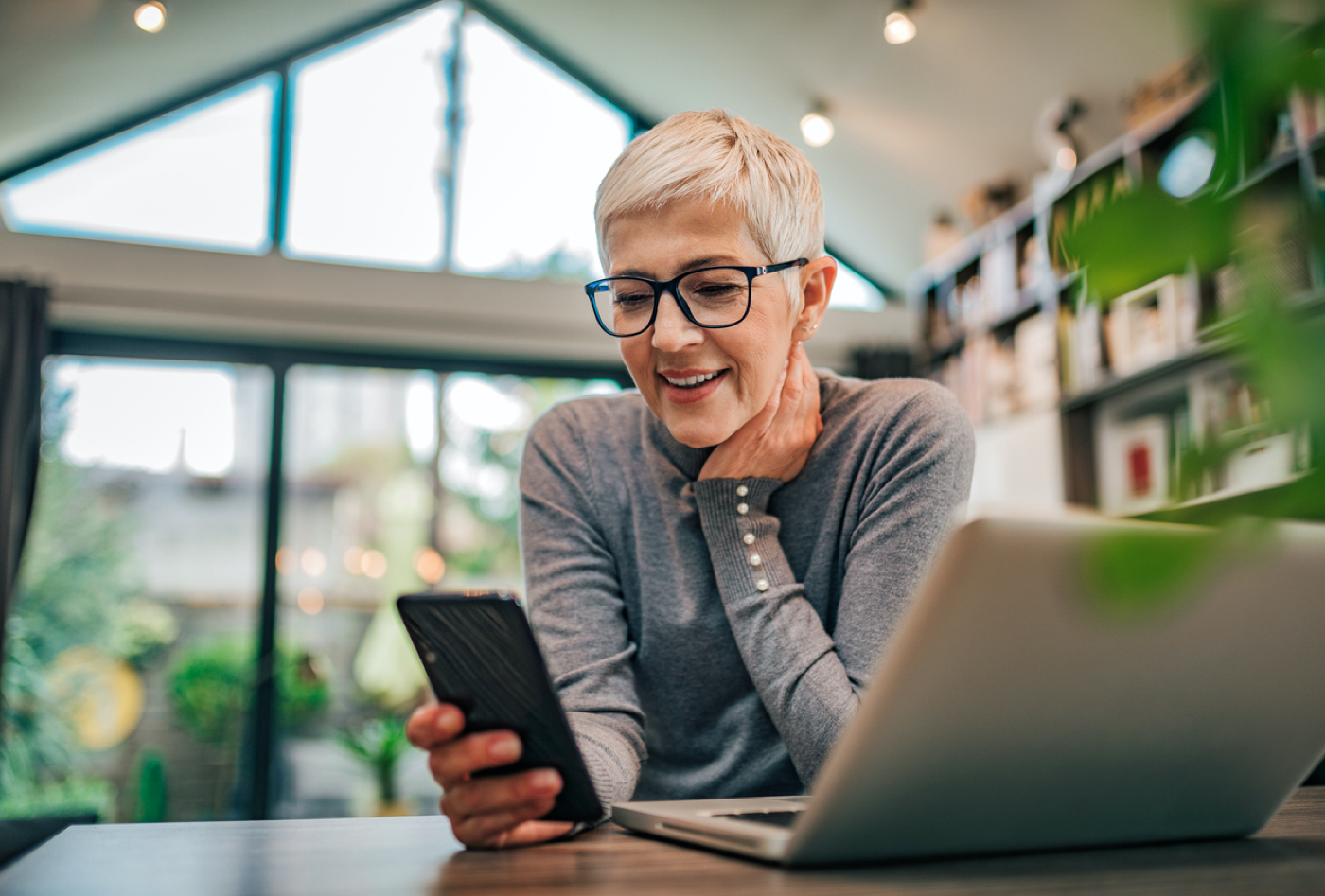 Smiling woman sitting at desk, looking at notification coming in on her smart phone