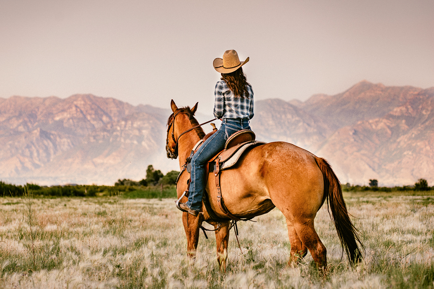 Cowgirl riding horse with mountain backdrop