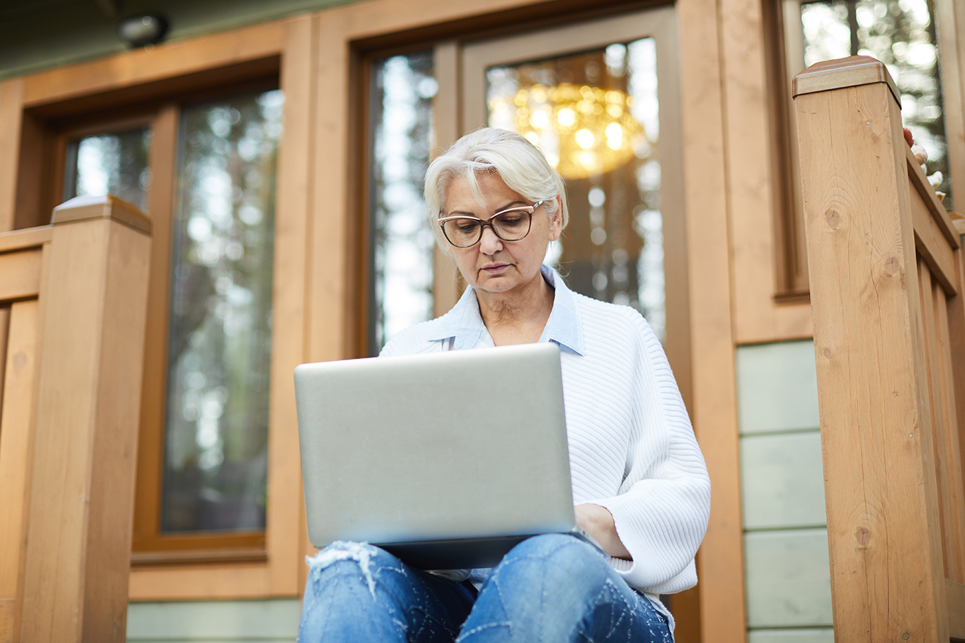 woman sitting on porch using laptop