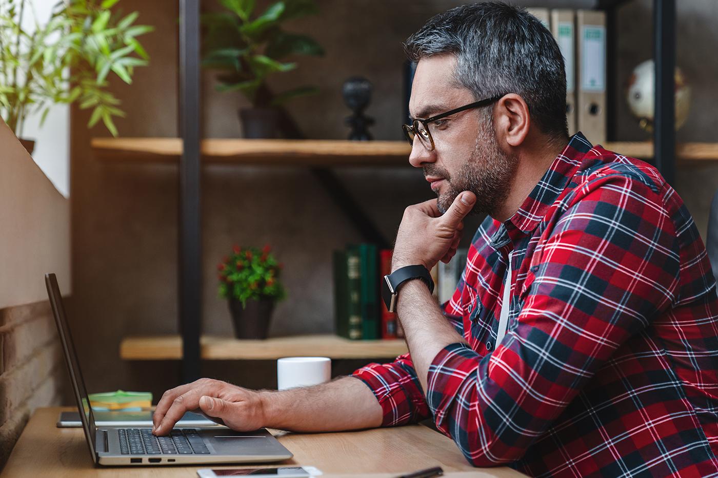 man at desk working on laptop
