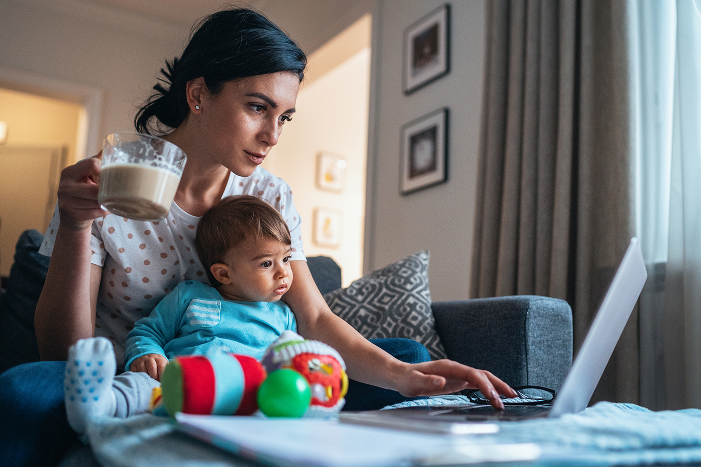 woman with baby on lap, working on laptop