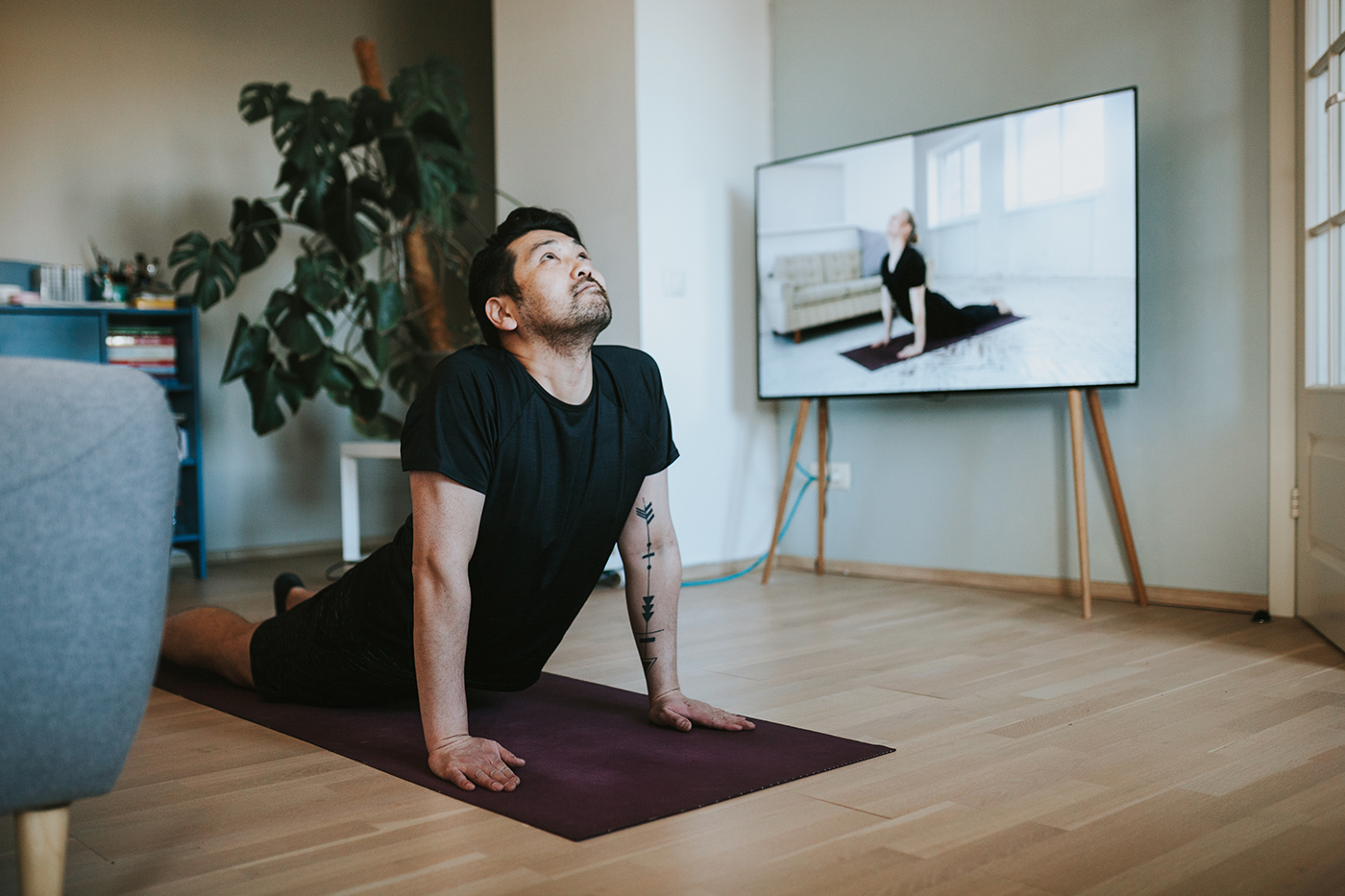 Man doing online yoga course in living room