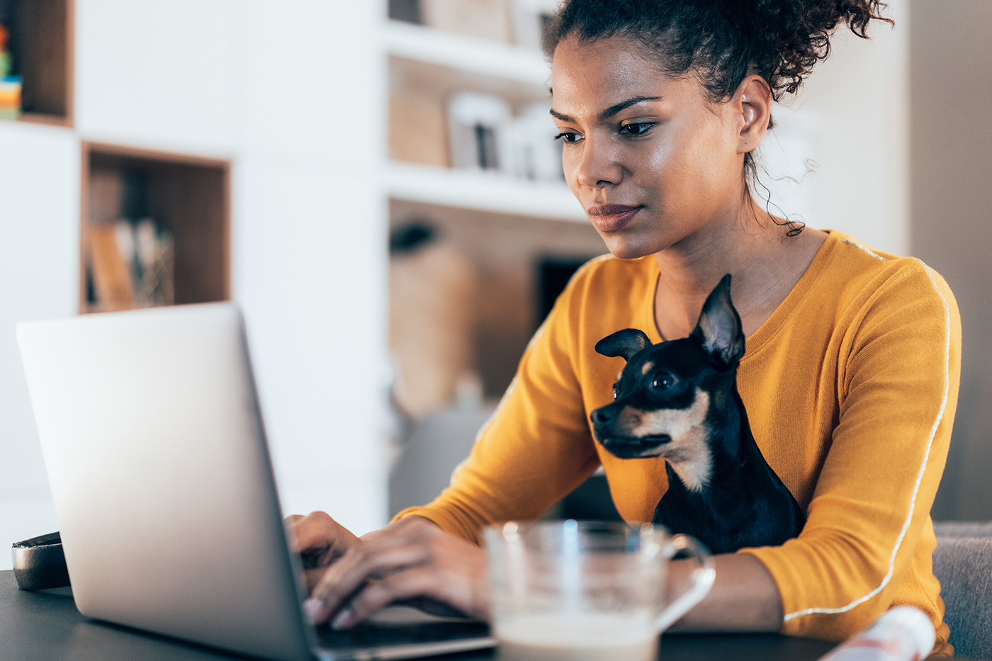 woman working on laptop with her dog