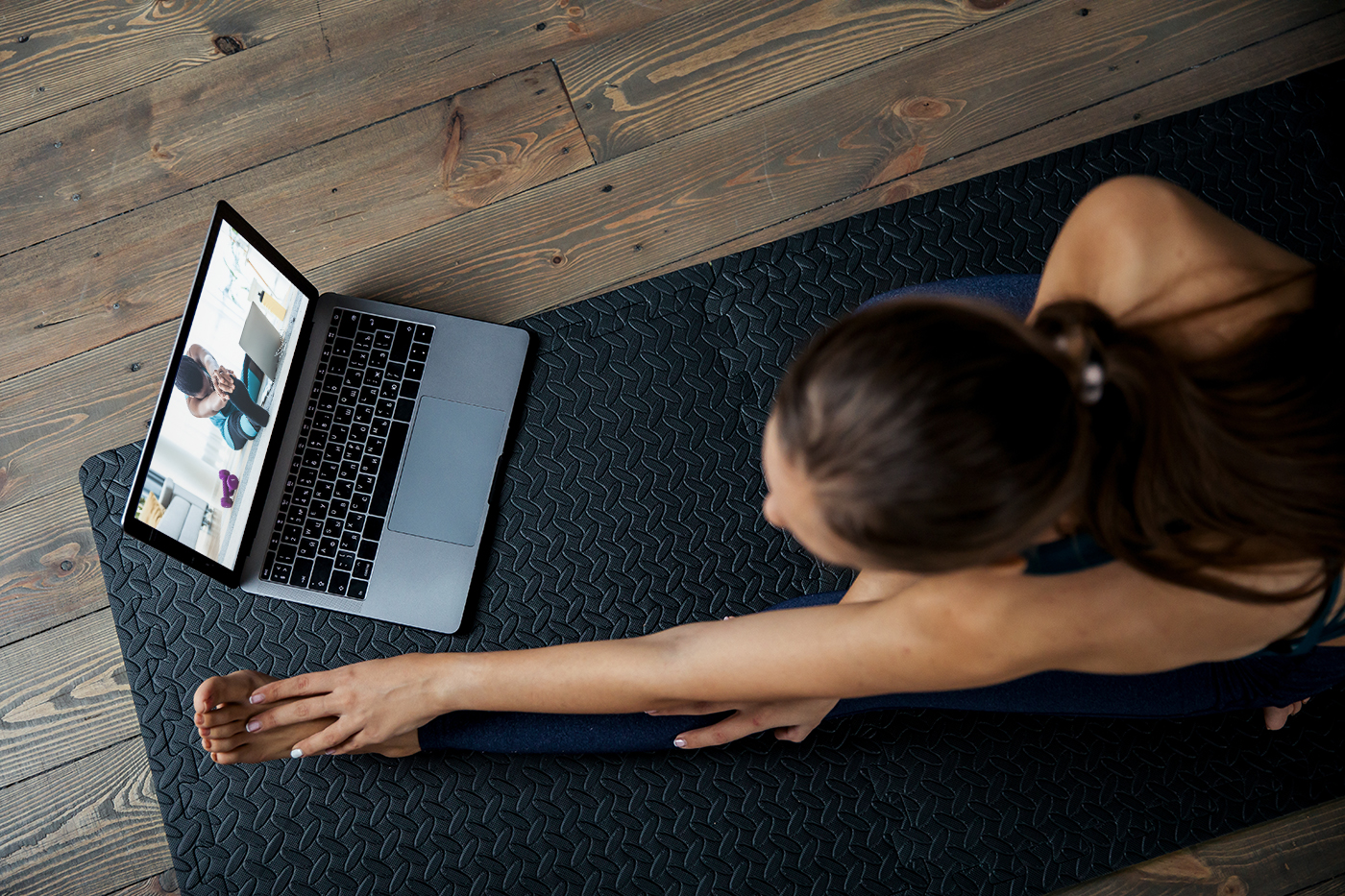 woman stretching on floor taking an online yoga course