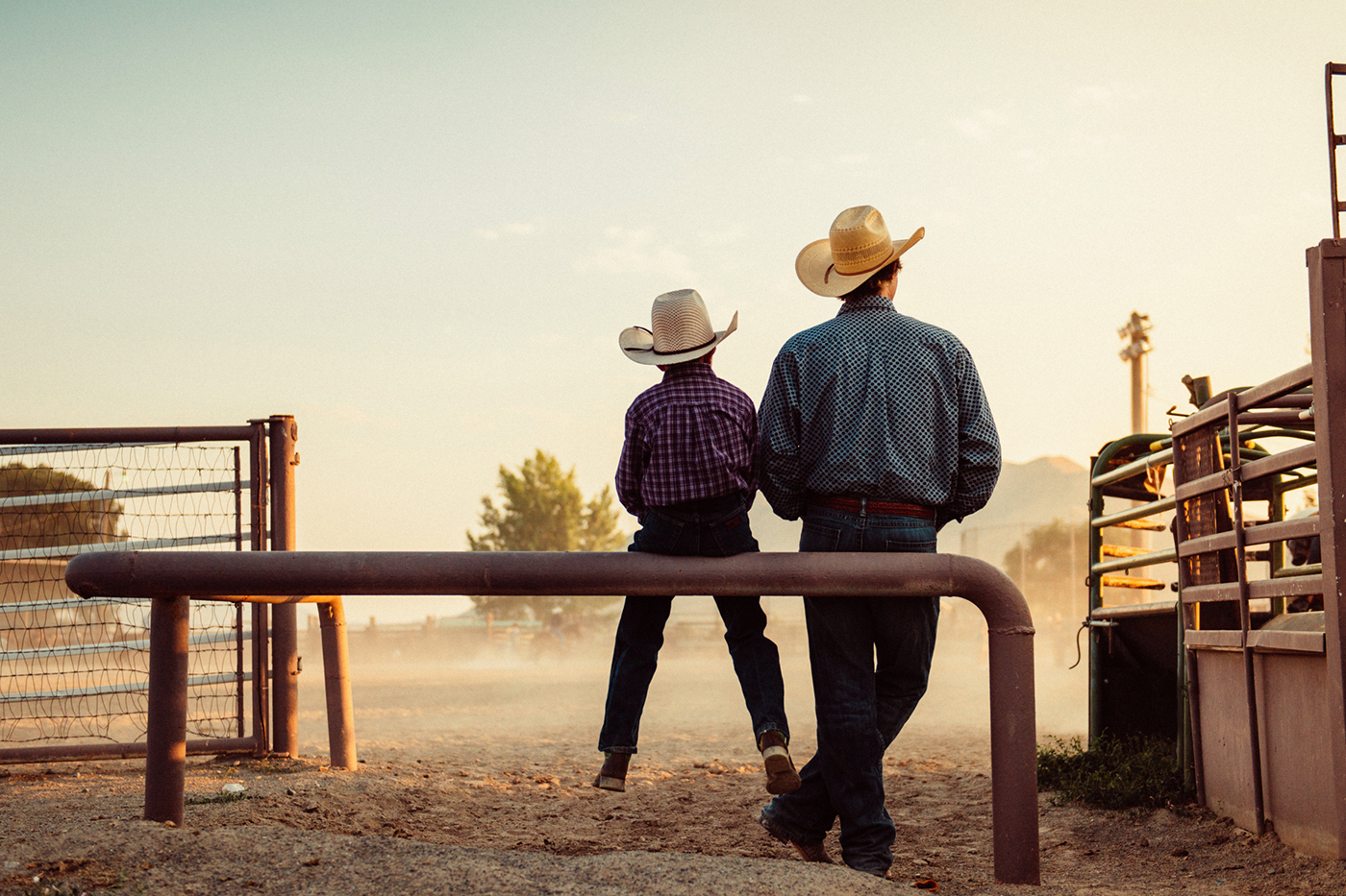 cowboy father and son watching rodeo
