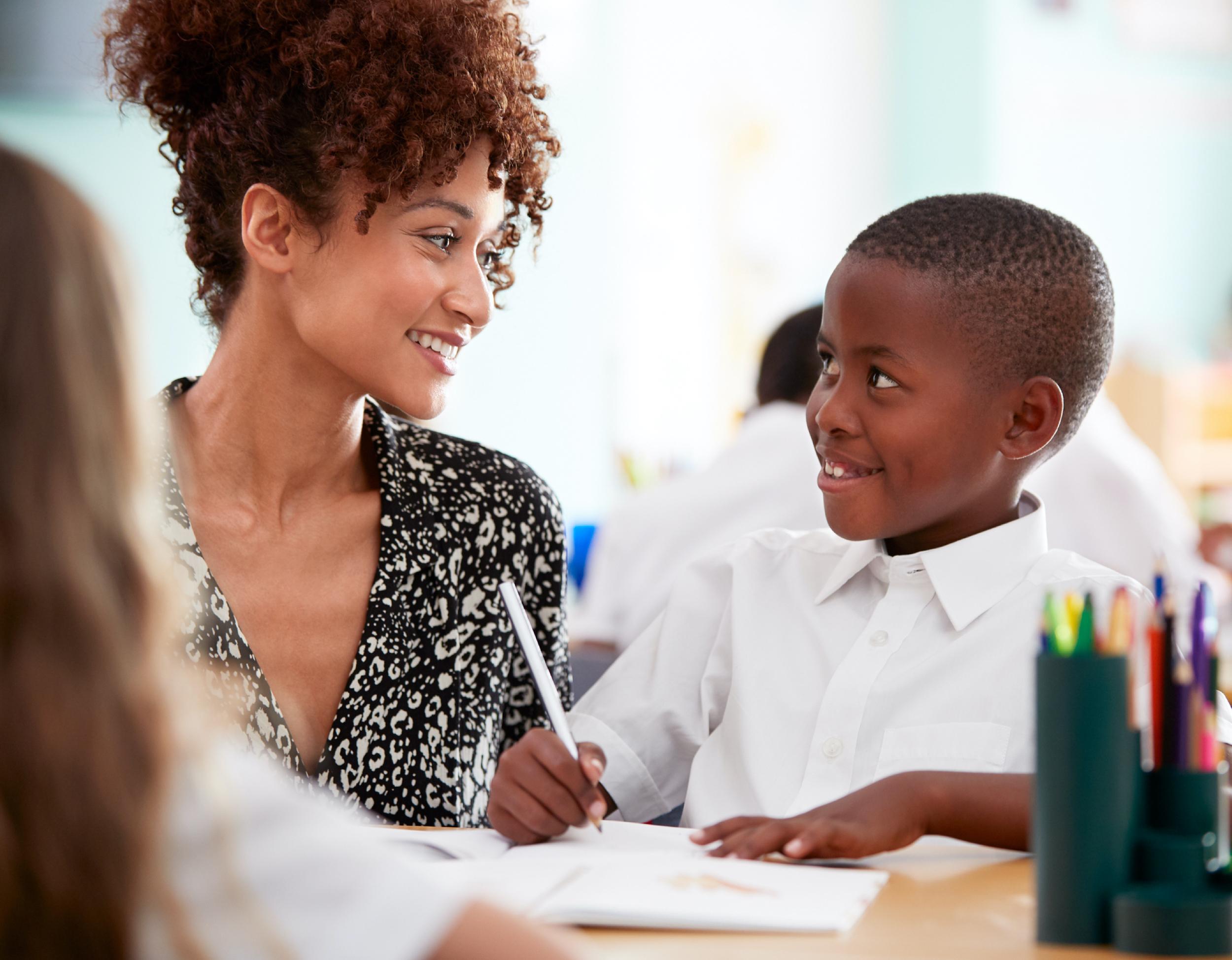 Smiling teacher helps student at desk