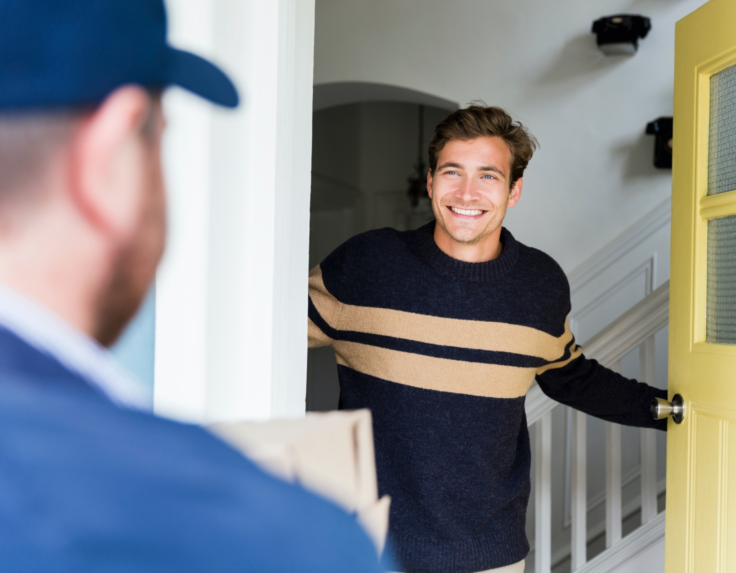 Young man opens front door of house for installation worker.