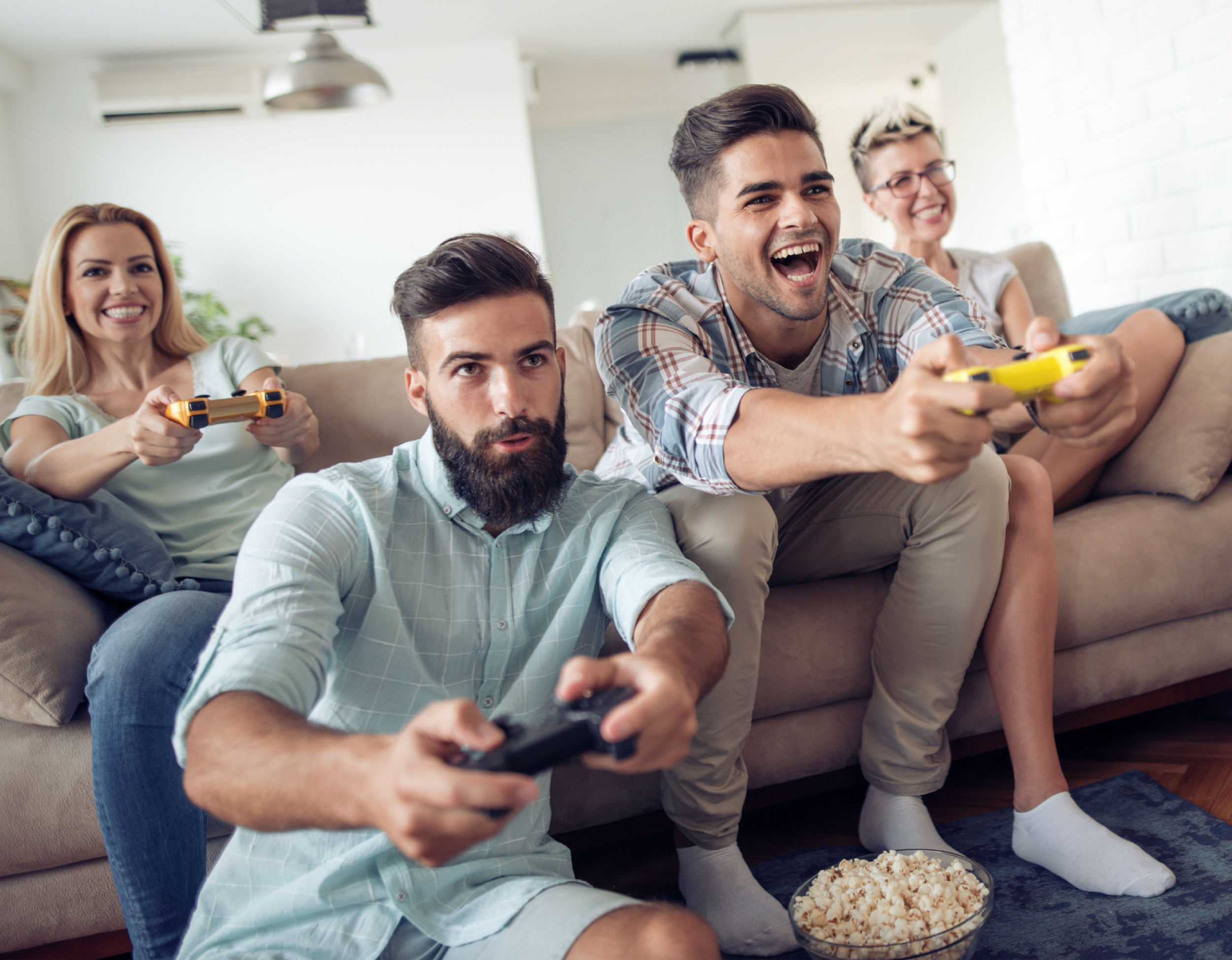 Friends playing video games together on a couch at home.