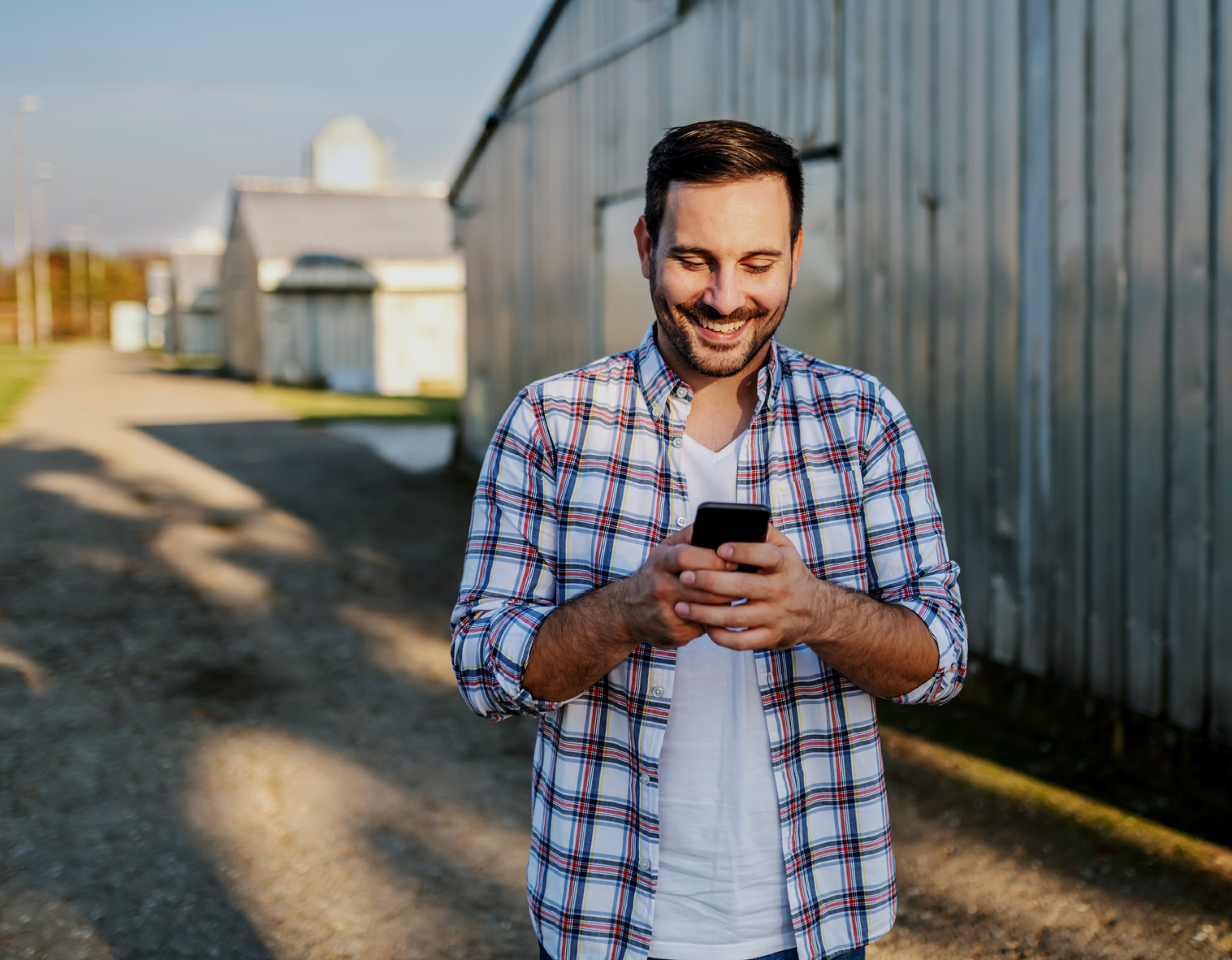 Happy young man walking on farm while looking at his cell phone.