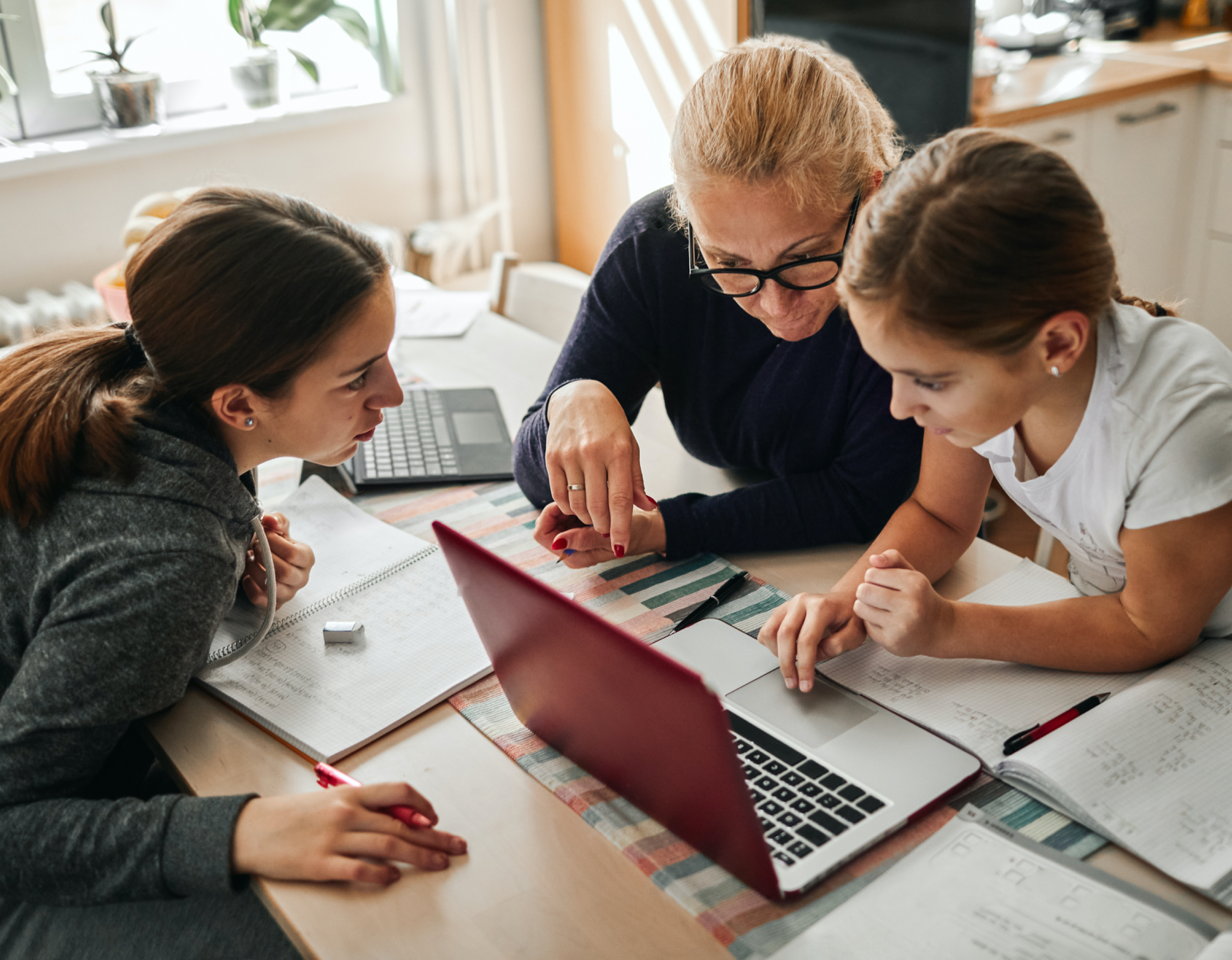 Mother and daughters work on homework together at table, with multiple tech devices.