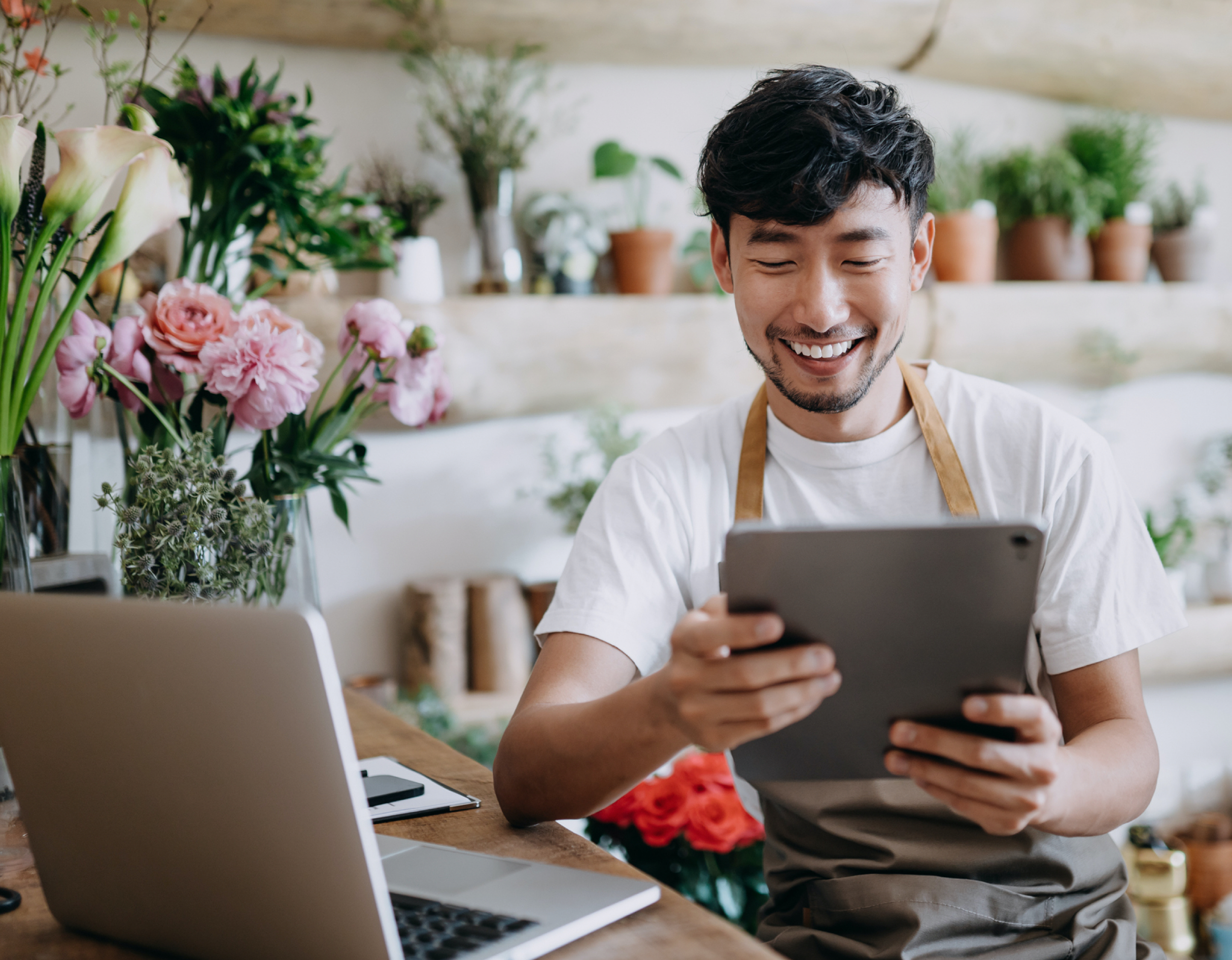 Happy man holding a tablet next to a laptop