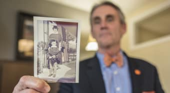 Man holding photo of his mother