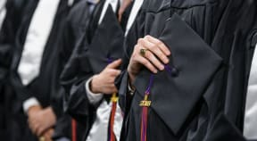 close up image of student holding his cap on his heart with the 2018 tassle showing