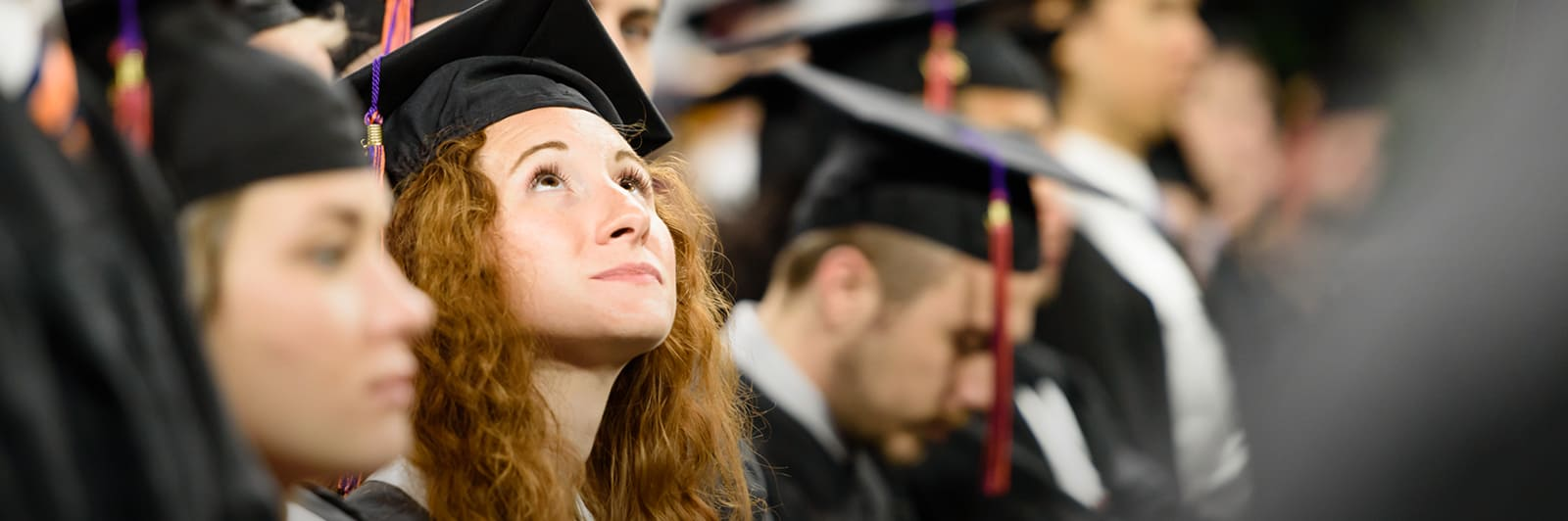 student wearing a cap and gown looks up while participating in a Clemson graduation ceremony.