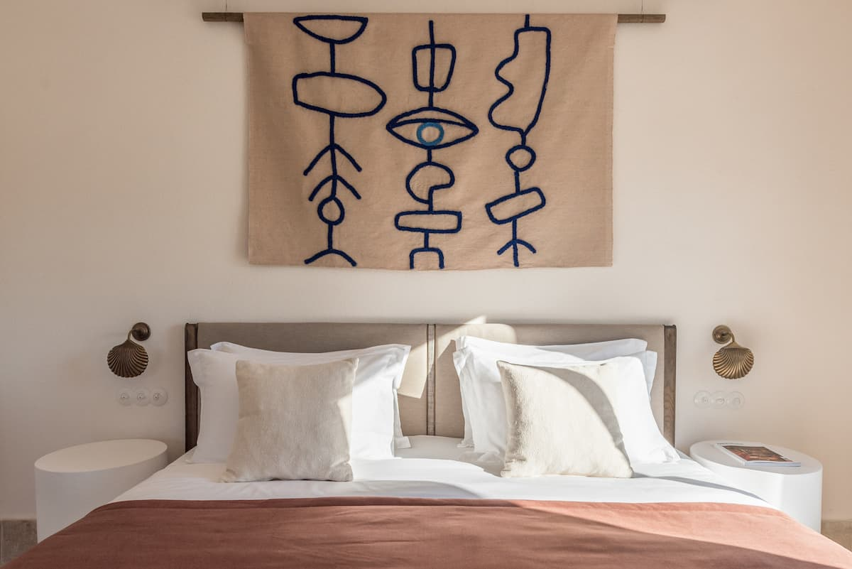 Bedroom with fabric artwork hanging over a bed