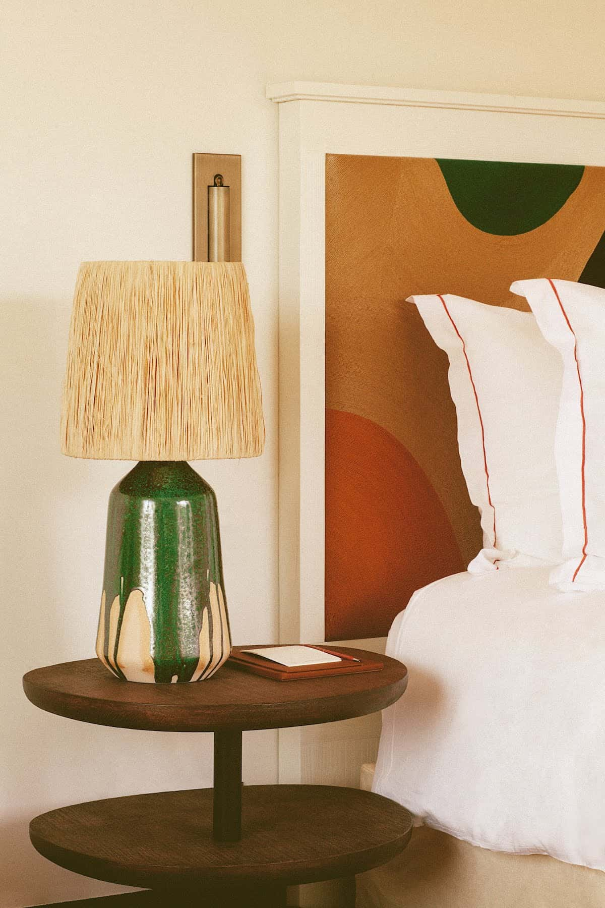 Lampshade with clay base on a sidetable next to a bed with colourful headboard in the Lou Pinet Hotel in St Tropez