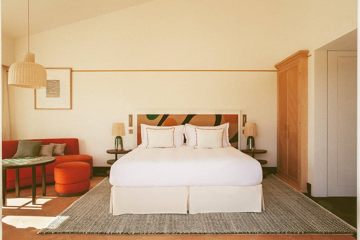 Bedroom with red sofa and colourful headboard in the Lou Pinet hotel in St Tropez