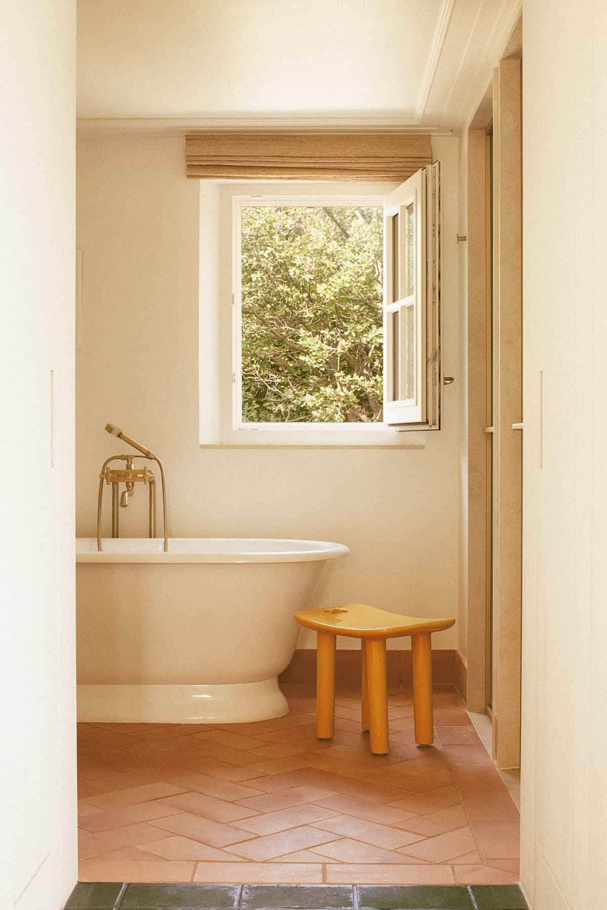 Bathroom with freestanding bathtub, a yellow stool and an open window overlooking green bushes