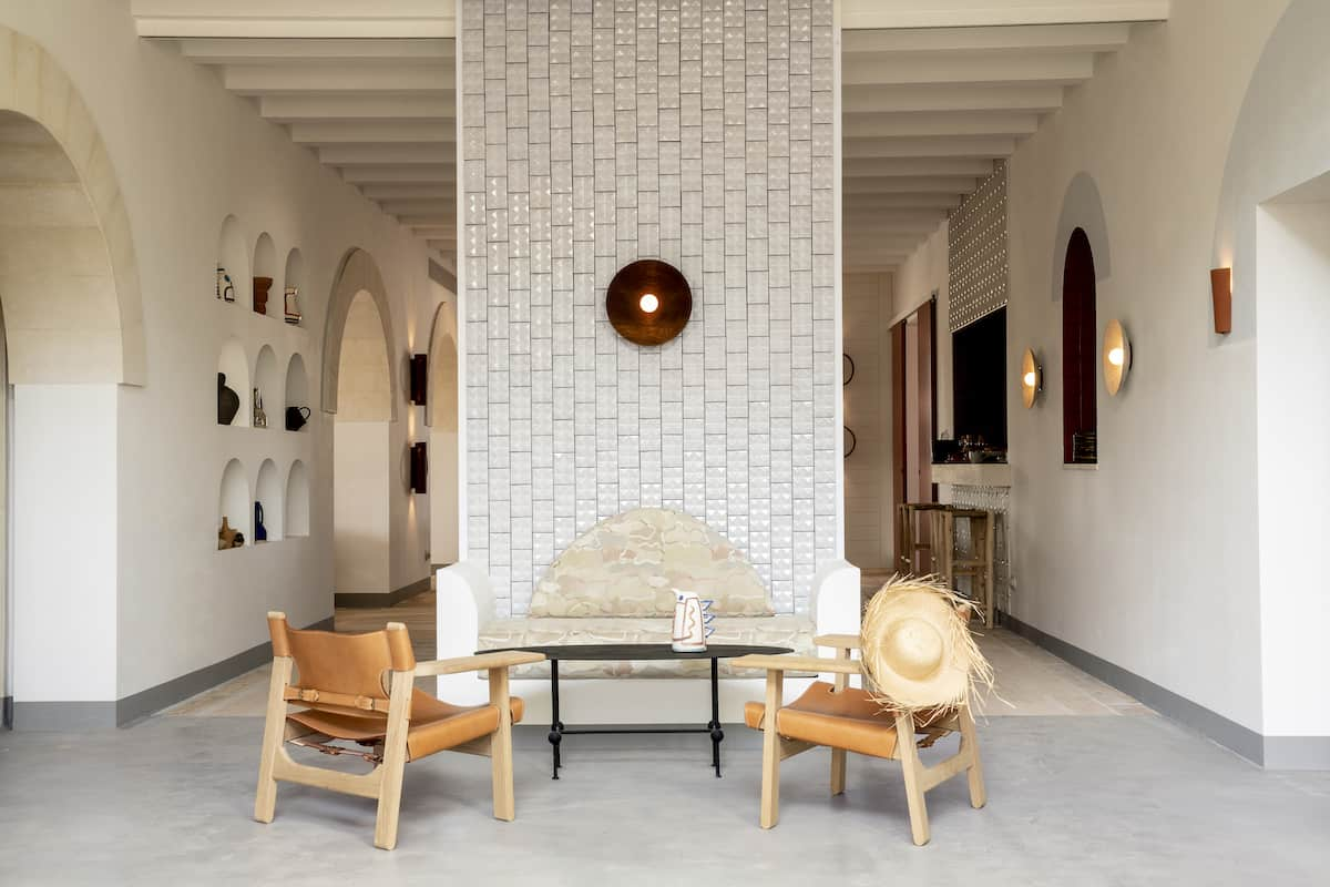 Lobby in the Hotel Experimental in Menorca with a tiled wall and leather chairs