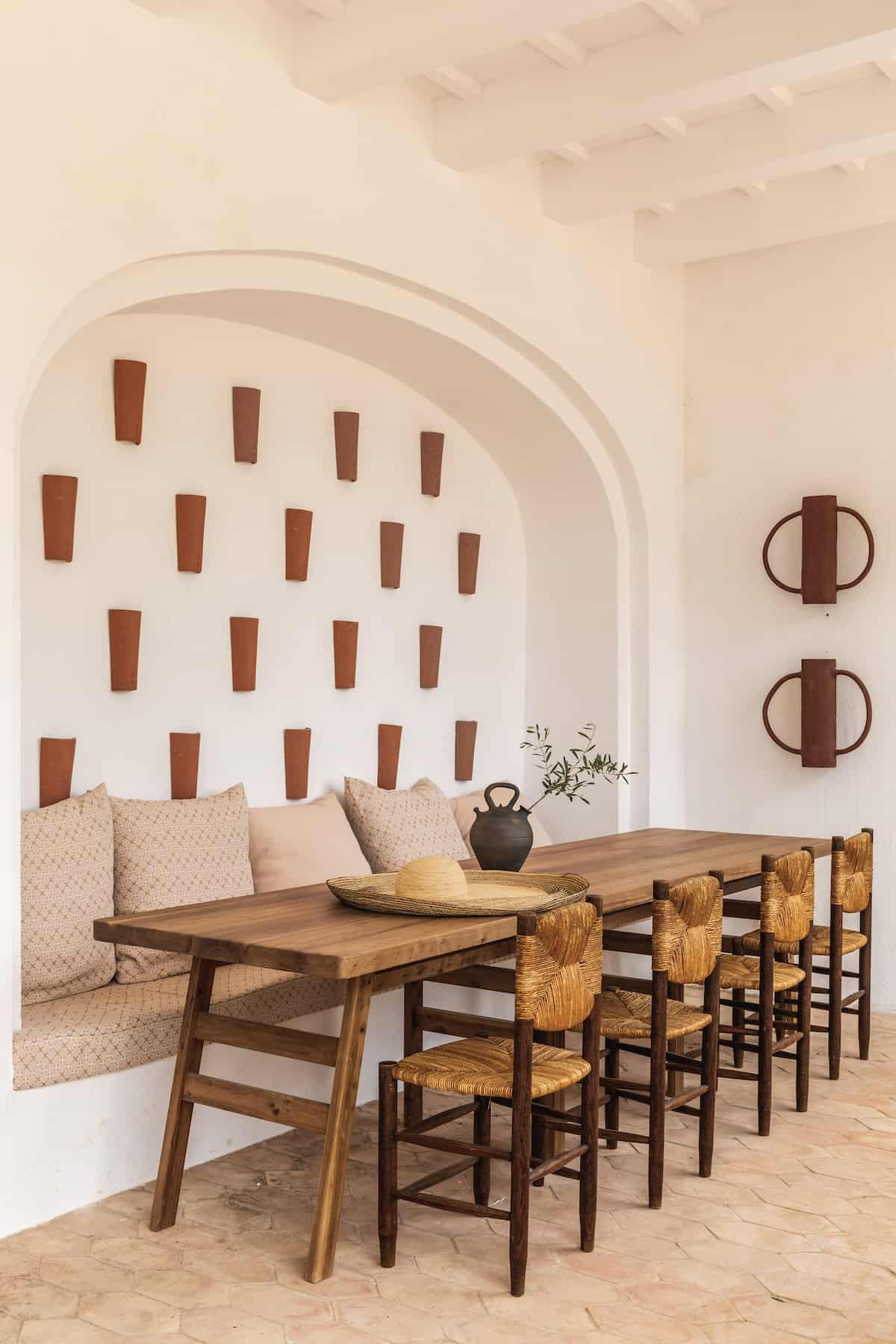 Dining table in the Hotel Experimental in Menorca with dark wooden chairs and a seating bench integrated into the wall.