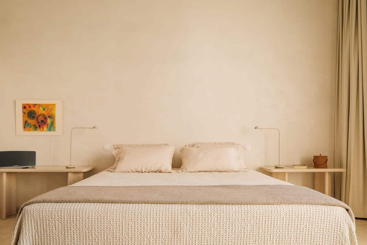 Beige bedroom with double bed and two bedside tables in the Da Licenza Boutique Hotel.