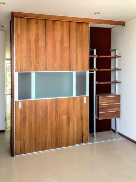 Closet con puertas y bicel de aluminio con cristal al centro.