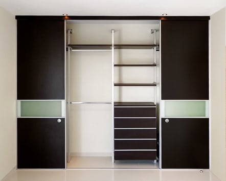 Closet color chocolate con puertas de aluminio y cristal.