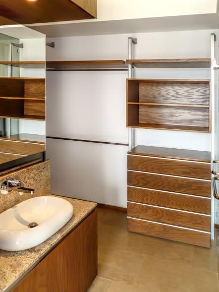 Closet vestidor de lujo de madera de encino instalado en baño.