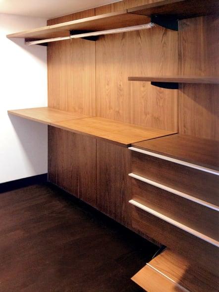 Closet vestidor minimalista de madera de nogal con acabado mate.