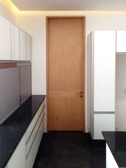 Puerta de baño de chapa de madera color natural.