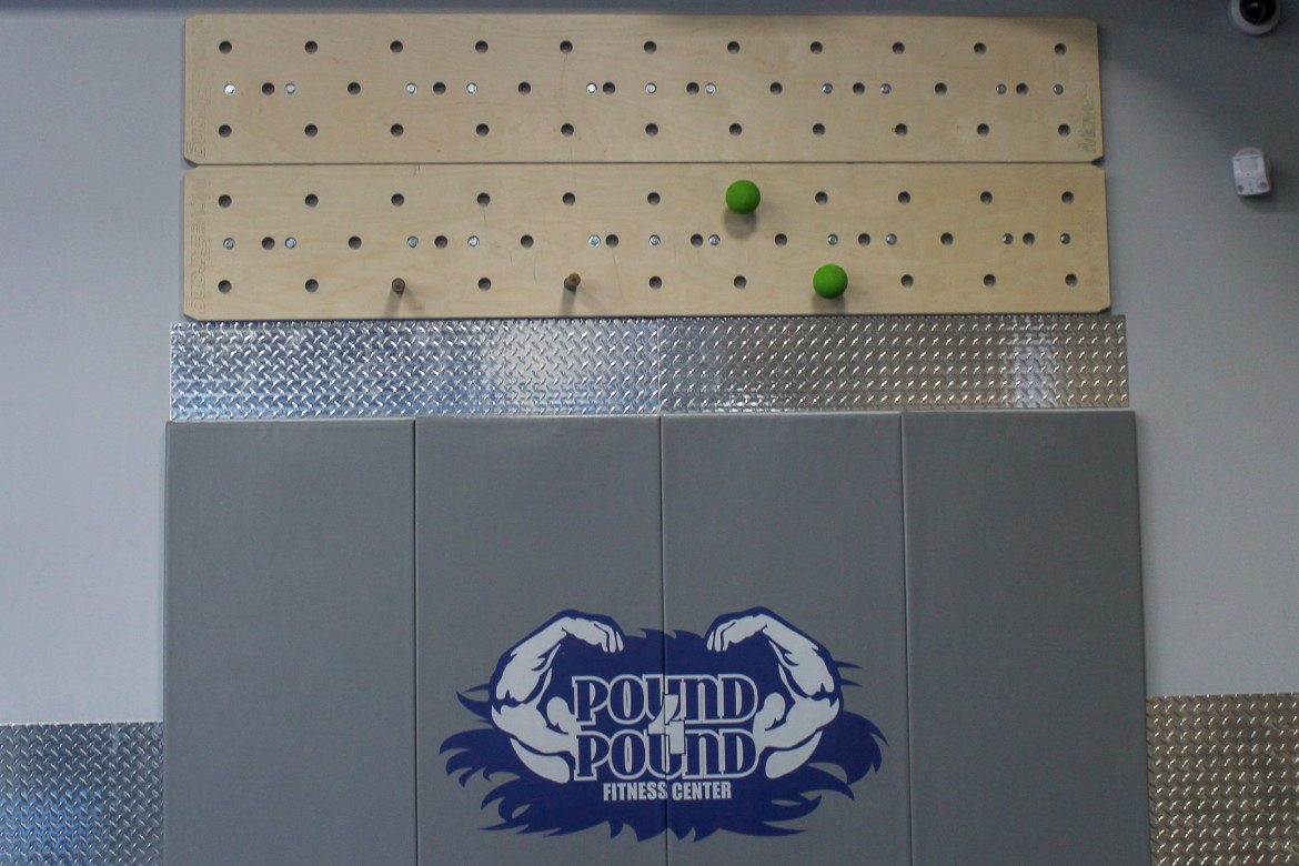 Peg Board above grey mat emblazoned with Pound 4 Pound logo in blue and white